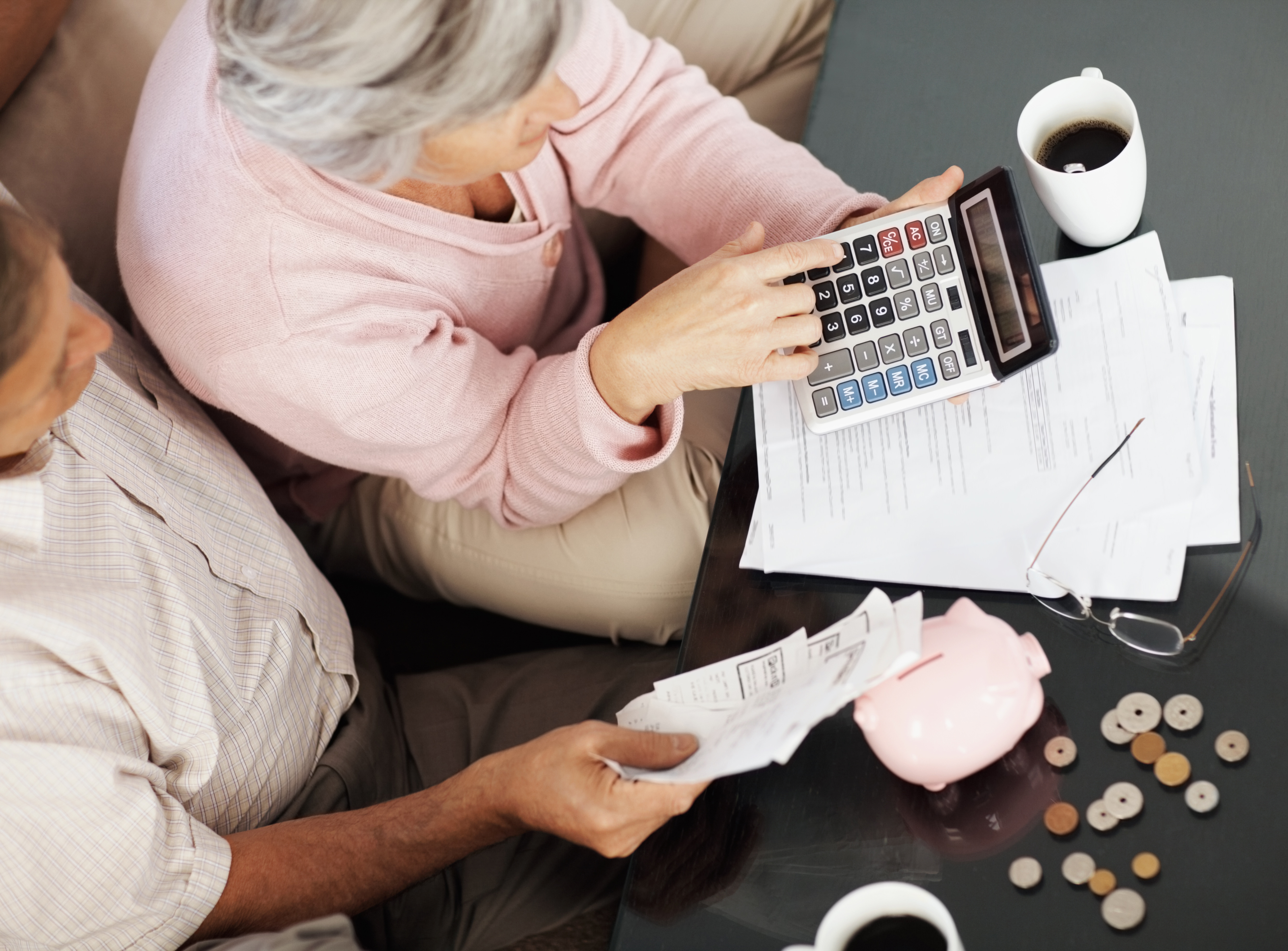 Elderly couple calculating their personal finances at home